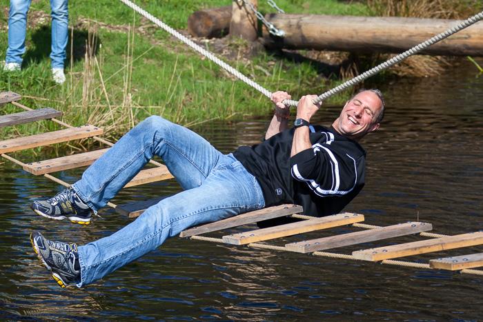 Iemand valt bijna in het water. Hij balanceert op een touwbrug boven het water. Een personeelsuitje waarbij veel wordt gelachen.