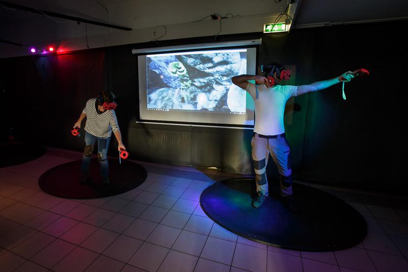 Groepsuitje VR-Room. 2 mensen met VR Bril en Beamer scherm